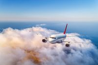 Passenger airplane flying over clouds at sunset