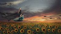 Fantasy portrait of young woman in long black dress flying on boat over sunflowers field at sunset time