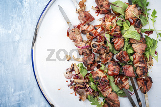 Traditional Russian shashlik on a barbecue skewer with roasted onion and lettuce as top view on tray with copy space left