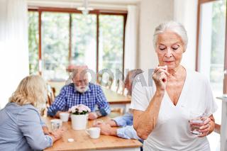 Seniorin im Altersheim nimmt eine Tablette ein