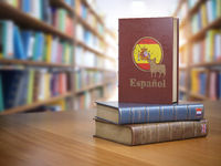 Learn Spanish concept. Spanish dictionary book or textbok with flag of Spain and cow on the cover in the library.