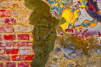 Weathered multicoloured wall with cement plaster