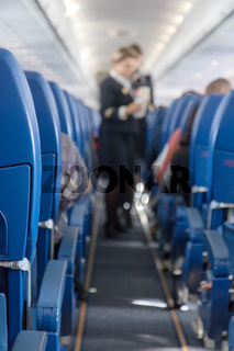The defocused stewardess serve refreshments on board the aircraft. An view at the corridor of the airplane.