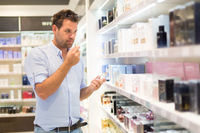 Elegant man choosing perfume in retail store.