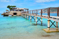 Wooden walkway leading across turquoise Mediterranean Sea