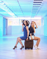 Two young women sit on  suitcases in the airport