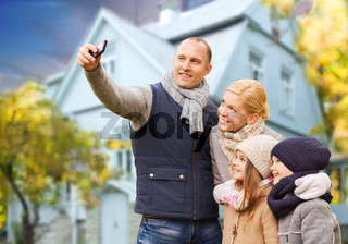 family takes autumn selfie by cellphone over house