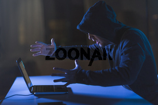 angry hacker with laptop computer in dark room