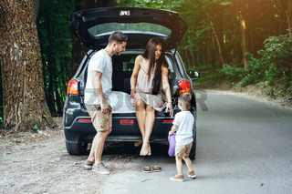 Young family near his car in the park.