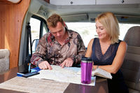 Middle aged married couple talking about future adventure planning route looking at map sitting in recreational vehicle motor home trailer. Active lifestyle