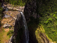 Aerial top view perspective of amazing 500 feet tall waterfall in the tropical island jungle of Mauritius.