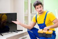Male professional serviceman repairing tv at home