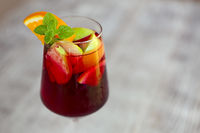 Glass of iced sangria with strawberry, orange, apple and lemon on the table