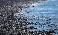 Black stone beach and deep blue sea.