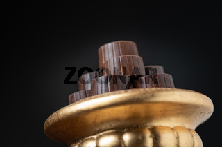 Stack of Fine Chocolates On Golden Pillar Dish With Dark Background