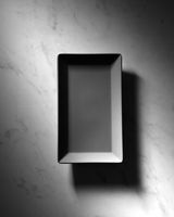Black rectangular empty plate presented on a gray marble background with shadows, space for text. Top view