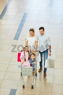 Eltern schieben Kinder im Einkaufswagen