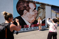 Tourists posing at Berlin Wall / East Side Gallery in front of Dimitri Vrubel`painting - of the the Fraternal Kiss (German: Bruderkuss)