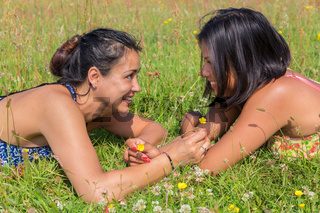 Two friends lying together in blooming meadow