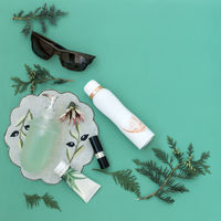 Cosmetics items on a light green background.