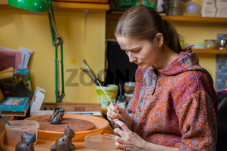 Professional woman potter painting ceramic souvenir penny whistle in pottery