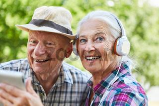 Paar Senioren mit Kopfhörer und Tablet