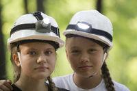 Portrait of cute teen sisters speleologists in helmets in summer