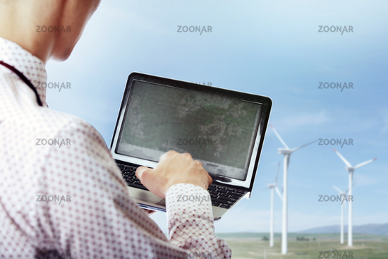 Businessman using laptop at the wind turbines site