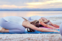 Group of young women do Child pose Balasana exercise outdoors