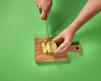 Wooman hands cut a juicy green ripe lime to slices with knife on a wooden cutting board on a green. Copy space.