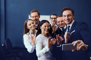 Smiling business people posing for selfie
