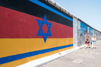 The Berlin Wall / East Side Gallery with painting combining the german and israeli flag
