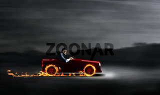Businessman in a red car with flames