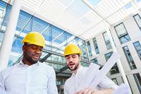 Zwei Architekten oder Bauleiter mit Bauplan