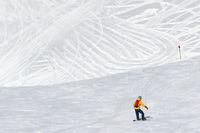 Snowboarder downhill on snowy ski trace