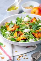 Salad with arugula, nectarines and pesto sauce.