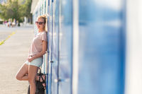 Blonde young female traveler wearing summer style clothing, leaning against retro blue beach dressing rooms at summer time vacation in Sistiana, Italy