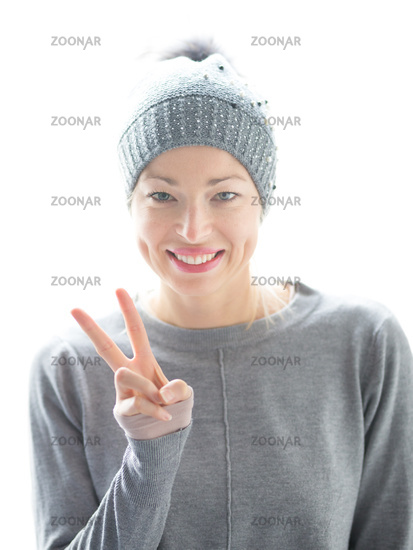Close up portrait of cheerful caucasian woman, gesturing peace sign and smiles