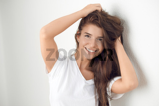 Young smiling blond woman leaning against wall