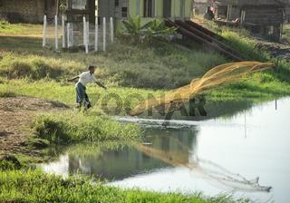 Silhouette of a fisherman throwing a fishnet in a lake. February 22, 2014 - Yangon, Myanmar