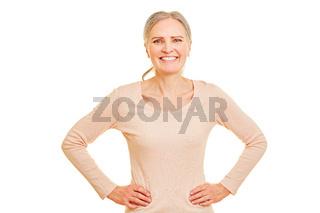 Glückliche ältere Frau mit Armen in der Hüfte