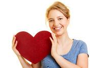 Junge Frau hält rotes Herz zum Muttertag