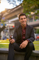Happy Hispanic businessman thinking while holding phone with nature in city