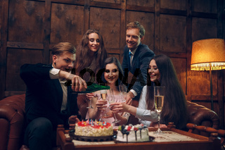 Cheerful friends celebrate birthday by drinking champagne and eating cake