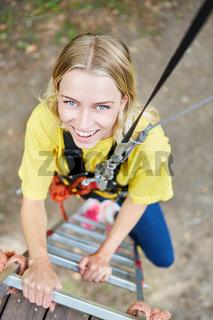 Junge Frau steigt eine Leiter im Hochseilgarten empor