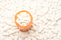 High angle view of a prescription bottled filled with pills surrounded by more of the same tablets