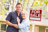 Caucasian Couple in Front of For Sale Real Estate Sign and House
