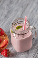 Milk smoothie with strawberries, mint leaves and chia seeds in a glass jar with a straw on a wooden table with copy space. Healthy drink