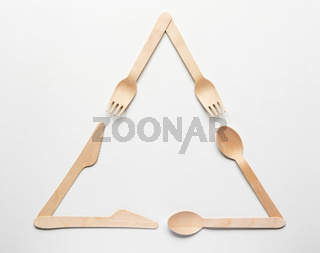 Wooden single use kitchenware in shape of Universal Recycling Symbol on white background. Top view