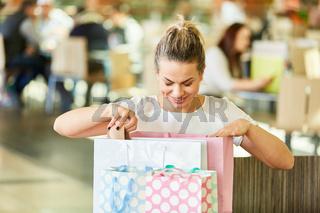 Frau schaut neugierig in Einkaufstüten